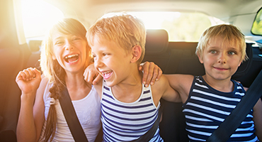 Three children sitting in the back seat of a car laughing