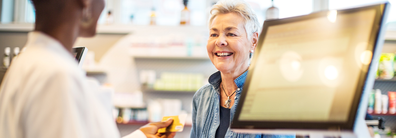 An older woman smiling as she talks to pharmacist.