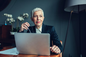 Older business woman sitting at a desk looking at a laptop