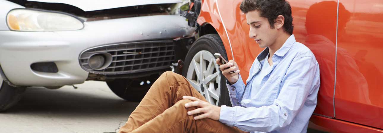 Man sitting on the ground with his phone in front of two vehicles that have hit each other