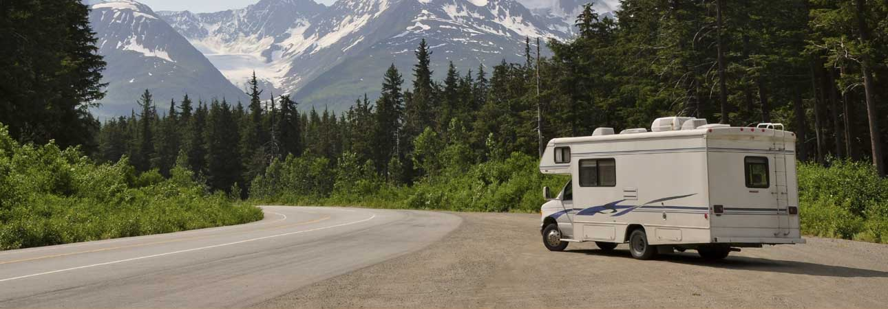 RV parked on the road with  mountains in the background