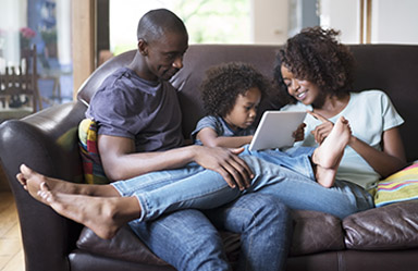 Mom, Dad and daughter sitting on couch looking at computer