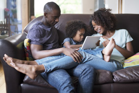 Mom, Dad and Daughter sitting on a couch looking at the computer